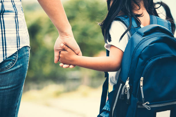 cute asian pupil girl with backpack holding her mother hand and going to school - school building stock photos and pictures