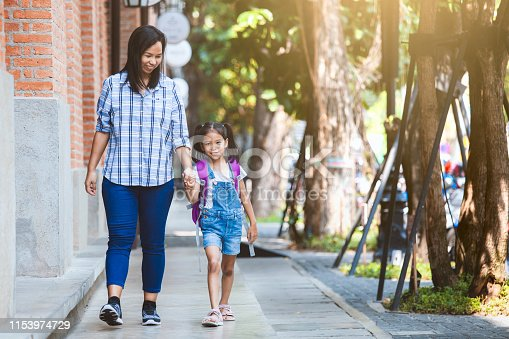Back to school. Cute asian pupil girl with backpack holding her mother hand and going to school