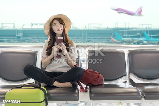 istock Cute asian student college traveler feeling happy action with travel plan and waiting for flight at airport terminal. Teenager travel concept. 692690534