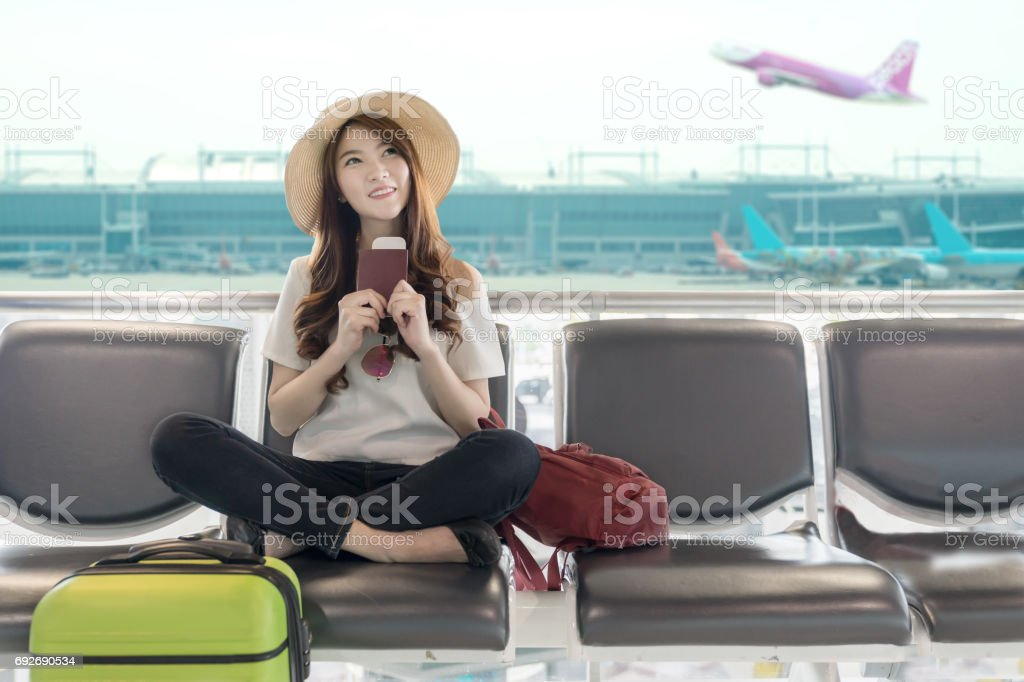 Cute asian student college traveler feeling happy action with travel plan and waiting for flight at airport terminal. Teenager travel concept. stock photo
