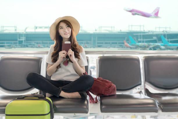 süße asiatische studentin college reisenden gefühl glücklich aktion mit reiseplan und abflug am flughafenterminal. teenager reisekonzept. - asienreise stock-fotos und bilder