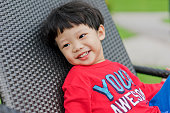 Portrait of little Asian boy smiling and sitting on a deckchair outdoor