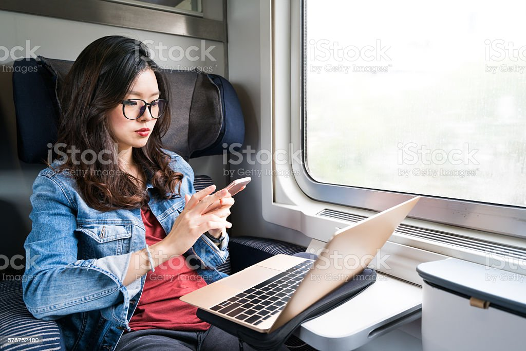 Cute Asian woman using smartphone and laptop on train stock photo