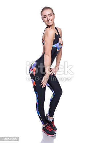 607622628istockphoto Cute athletic girl posing in the studio isolated on white background. Young woman bodybuilder or fitness coach wearing sportswear tracksuit. 658549056