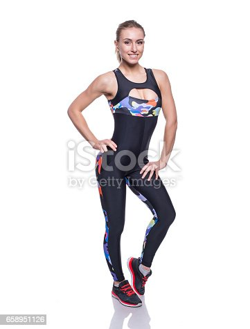607622628istockphoto Cute athletic girl posing in the studio isolated on white background. Young woman bodybuilder or fitness coach wearing sportswear tracksuit. 658951126