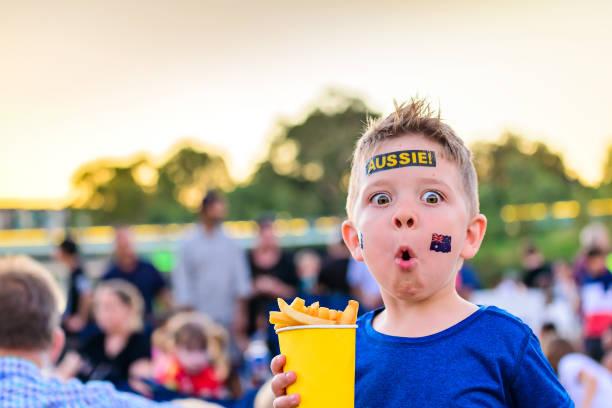 Netter australischer Junge mit Fahne-Tattoo auf seinem Gesicht – Foto