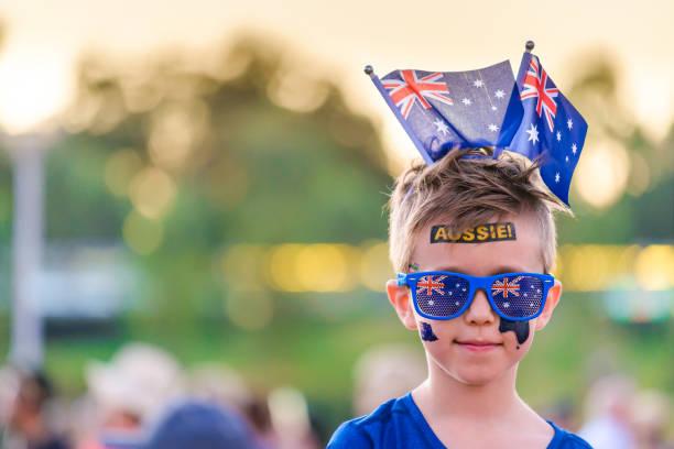 Netter australischer Junge mit Fahnen und Tätowierungen auf seinem Gesicht – Foto