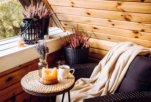 Cute autumn home decor arrangement. Tiny wooden cabin balcony with heather flowers in pot, lavender in bottle vase, candlelight flame, soft beige plaid waiting on comfortable garden furniture chair.