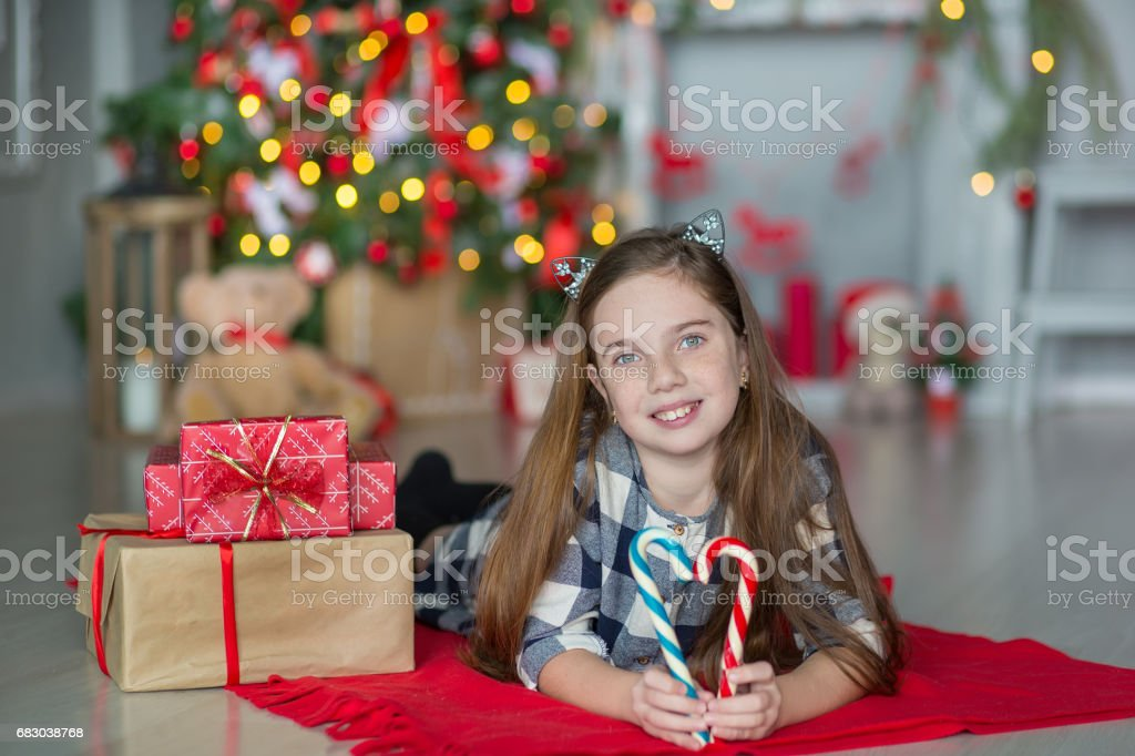 Cute awesome girl celebrating New Year Christmas close to xmas tree full of toys in stylish dresses with candies foto de stock royalty-free