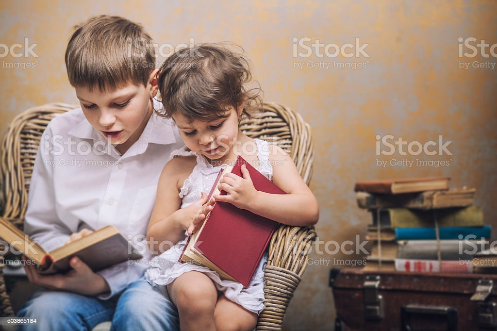 Cute babies boy and girl in a chair reading stock photo