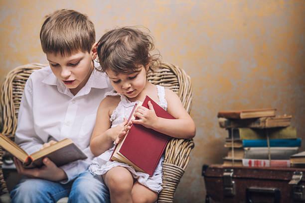 かわいい赤ちゃん男の子と女の子の椅子で読書 - 兄弟 ストックフォトと画像