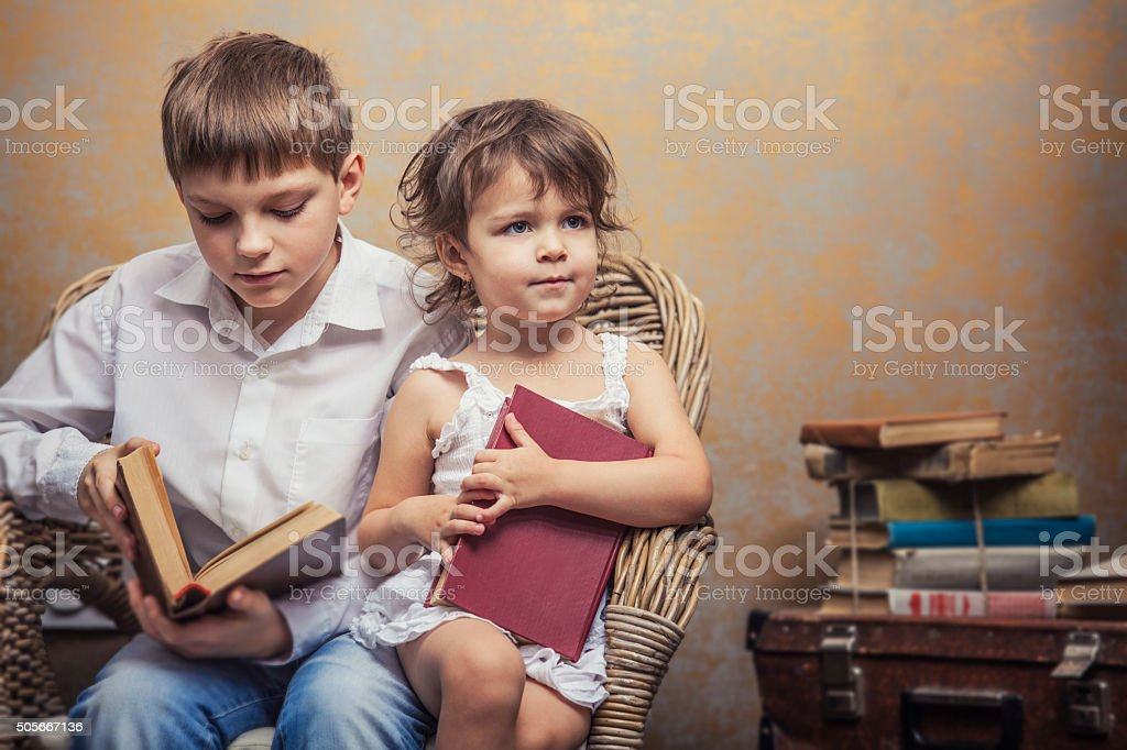 Cute babies boy and girl reading a book stock photo