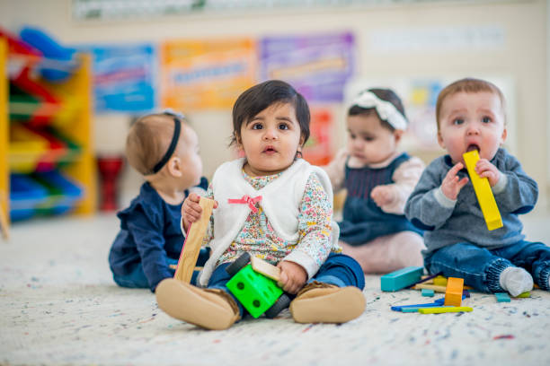 Cute babies playing on a carpet stock photo