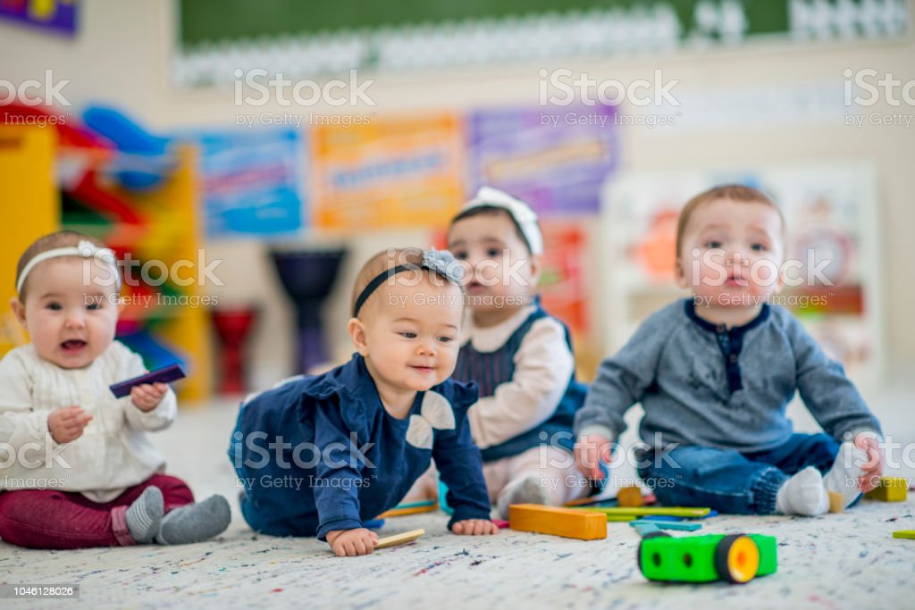 Cute babies playing with toys in daycare stock photo