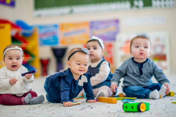 Cute babies playing with toys in daycare A 1 year old girl crawls on the carpet while smiling. A group of babies sitting next to her look around curiously. They are in a colorful daycare environment. babies only stock pictures, royalty-free photos & images