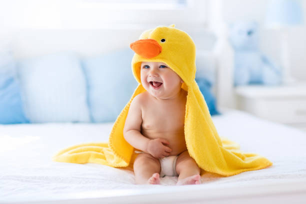 Cute baby after bath in yellow duck towel - foto stock
