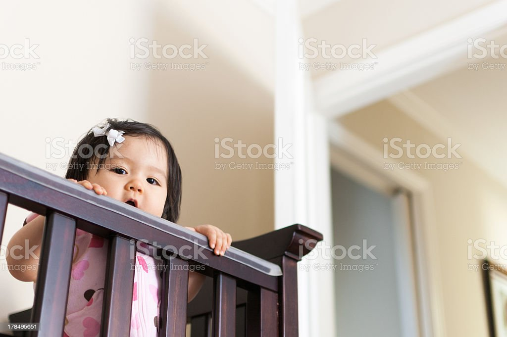 Cute Baby Asian girl peering out from her crib stock photo