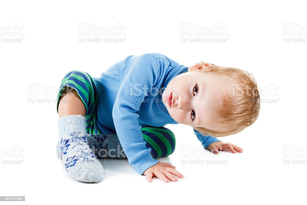 Cute baby blonde in a blue sweater playing on white stock photo