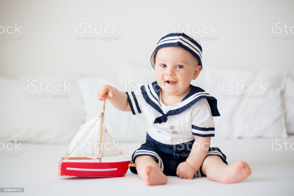 Cute baby boy, dressed in sailor clothes, playing with wooden boat stock photo