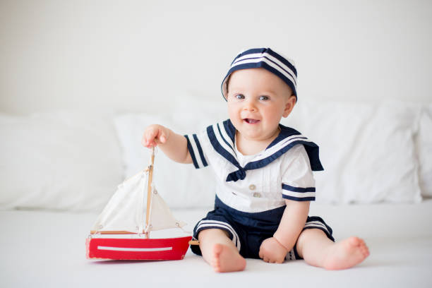 Cute baby boy, dressed in sailor clothes, playing with wooden boat Cute baby boy, dressed in sailor clothes, playing with wooden boat sailor stock pictures, royalty-free photos & images