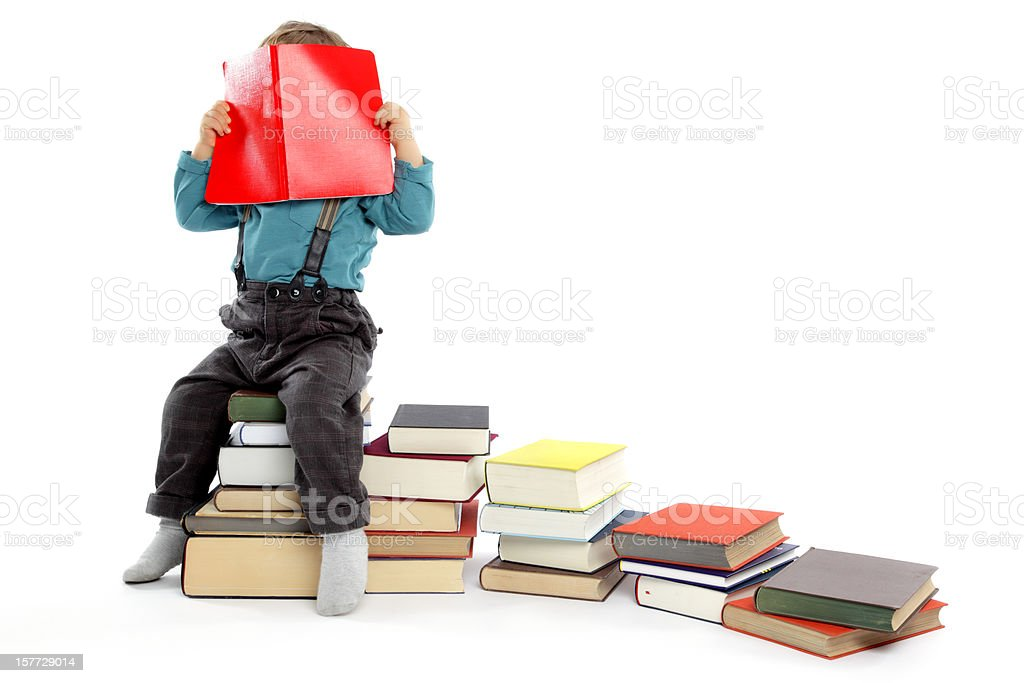 Cute baby Boy hiding behind a Big Red Book. royalty-free stock photo