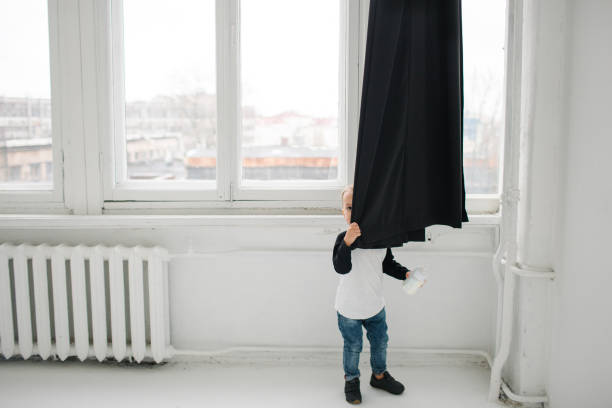 Cute baby boy hiding over curtains in white apartment – Foto