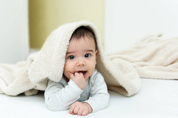 Cute baby boy in bed under a fluffy blanket stock photo