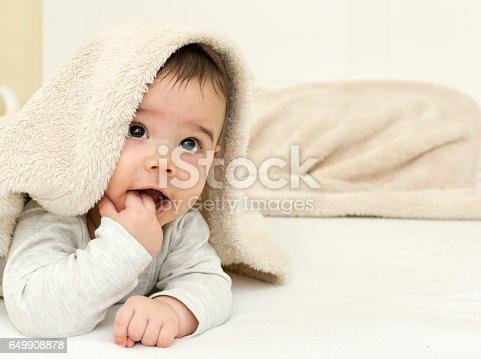 Cute baby boy in bed under a fluffy blanket