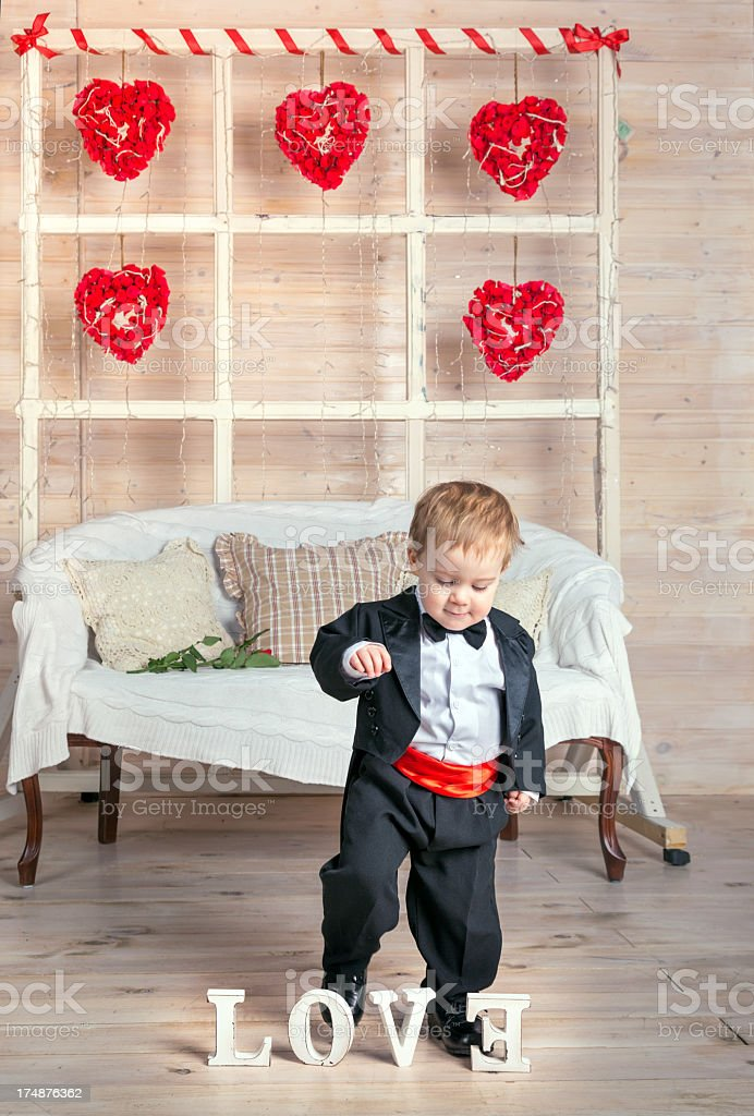 Cute baby boy in black tuxedo and inscription LOVE royalty-free stock photo