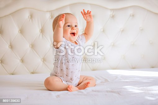 istock Cute baby boy in white sunny bedroom 869139630