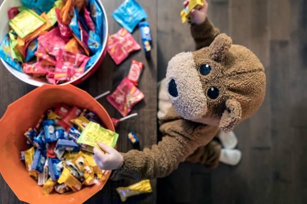 niedliche baby boy in bär kostüm essen oder süßigkeiten greifen - süßigkeit stock-fotos und bilder