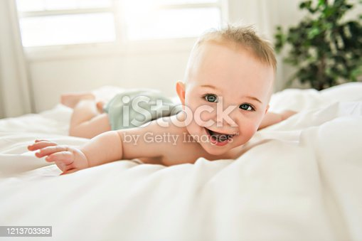 A cute baby boy lying on a white bed