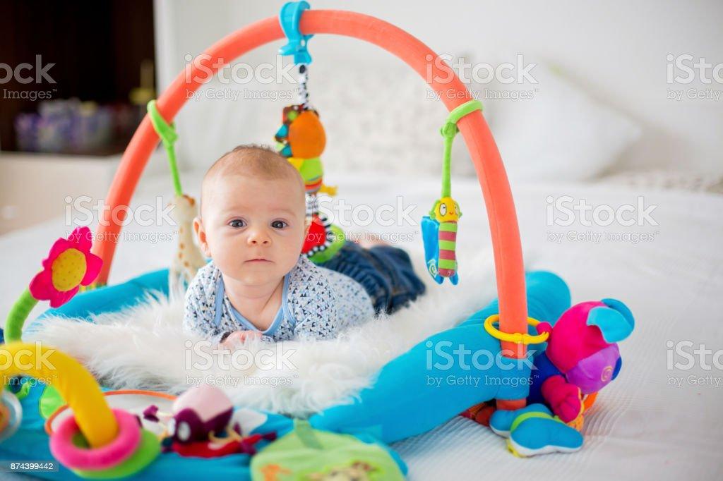 Menino bonito no ginásio colorido, brincar com brinquedos em casa de suspensão - Foto de stock de Abdome royalty-free