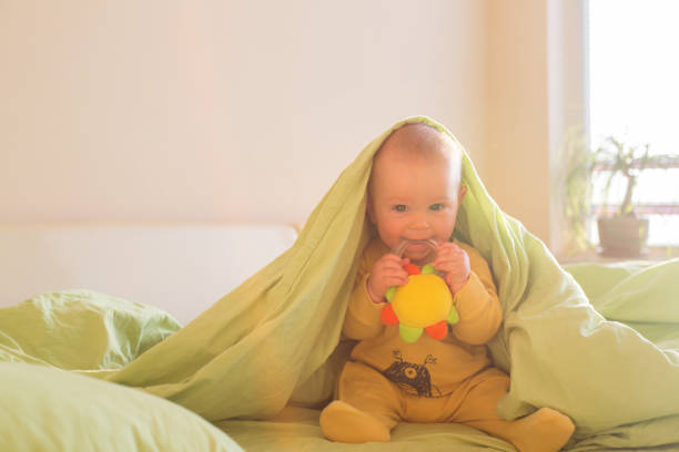 Cute baby boy, playing in bed morning time stock photo
