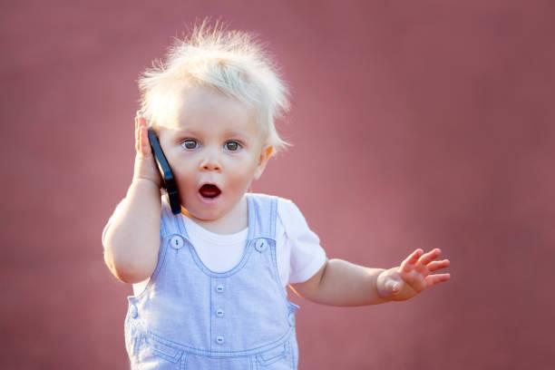 Chico lindo bebé jugando con el teléfono móvil en el parque, las tecnologías digitales en las manos de un niño - foto de stock