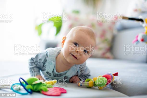 Cute baby boy playing with toys in a sunny living room picture id871598028?b=1&k=6&m=871598028&s=612x612&h=s khnsn12bspaew3evzsbkf cc vwfux0rlazzldkzq=