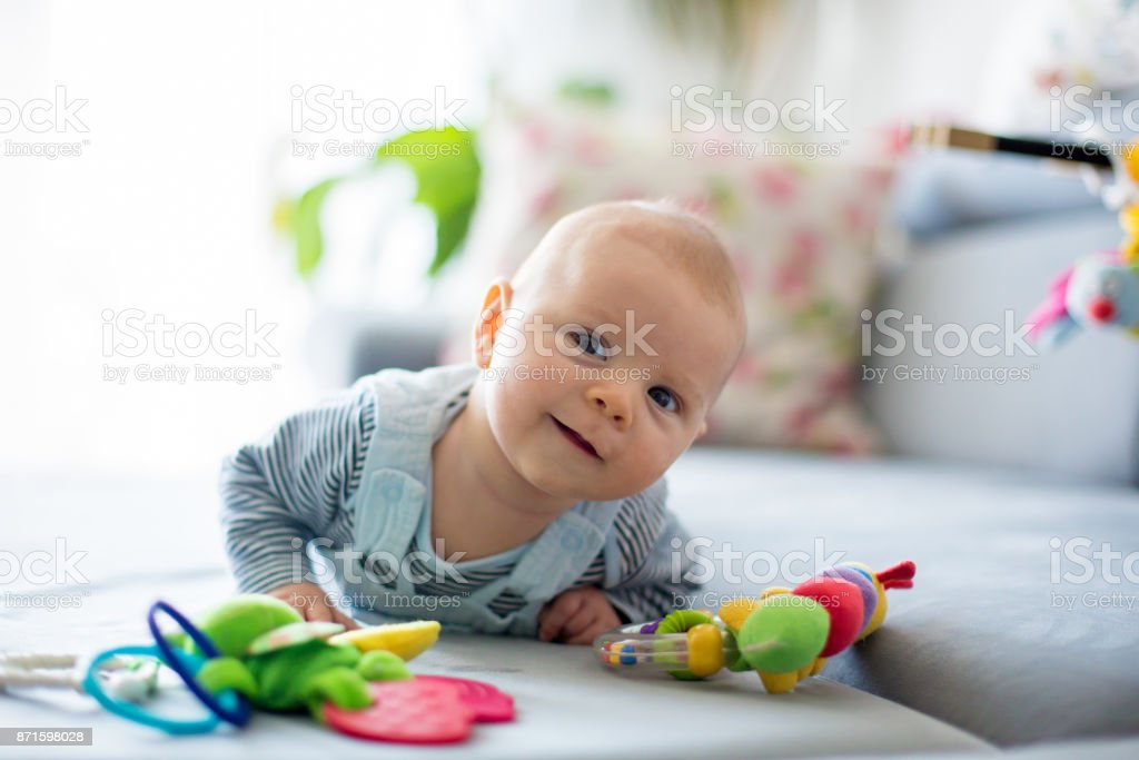 Cute baby boy, playing with toys in a sunny living room stock photo