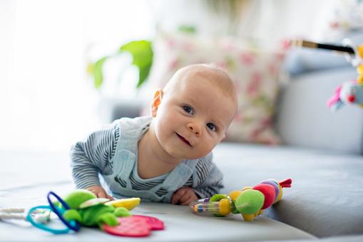 Foto de Menino Bonito Brincando Com Brinquedos Em Uma Sala De Estar Ensolarado e mais fotos de stock de Abdome