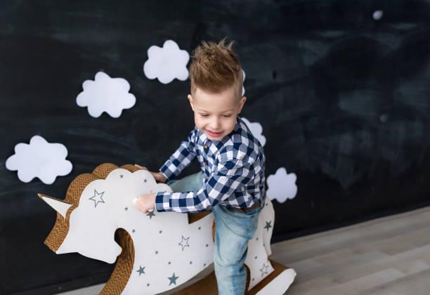 nette sanien junge reiten holz traditionelle schaukelpferd spielzeug im zimmer. kind spielt im kinderzimmer. - pferde schlafzimmer stock-fotos und bilder