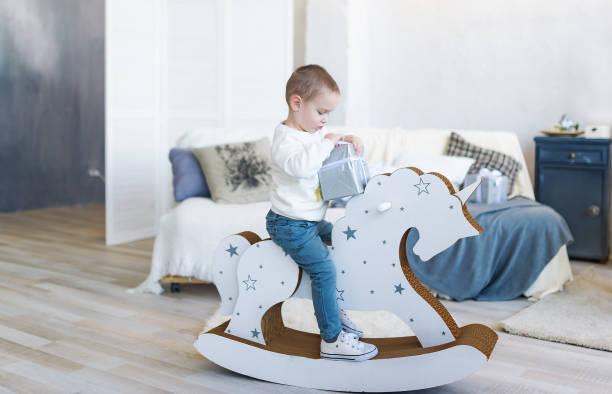 nette sanien junge reiten holz traditionelle schaukelpferd spielzeug in weißen schlafzimmer. kind spielt im kinderzimmer. - pferde schlafzimmer stock-fotos und bilder