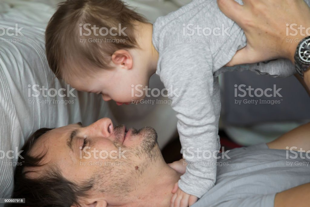 Cute baby boy with Down syndrome playing with dad stock photo