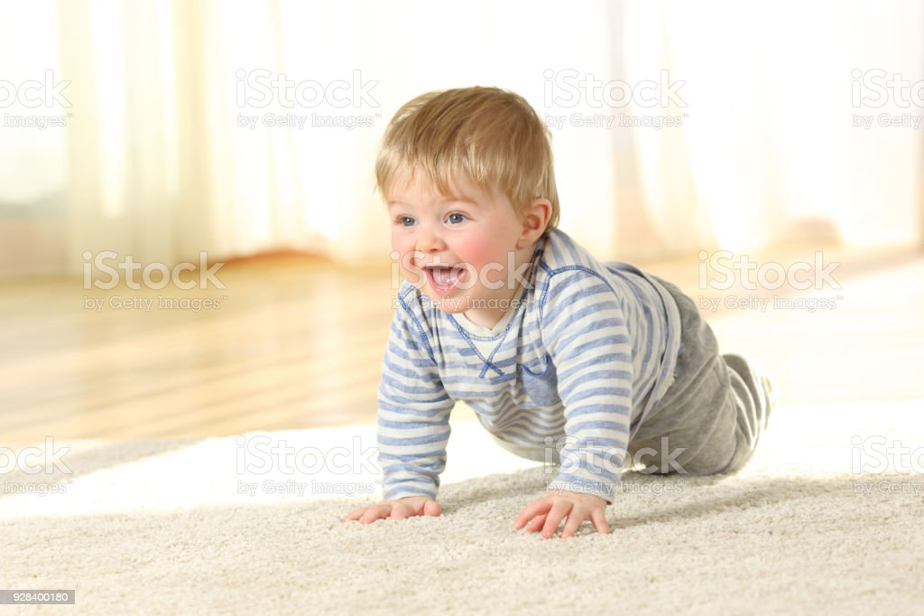 Cute baby crawling and laughing on the floor stock photo