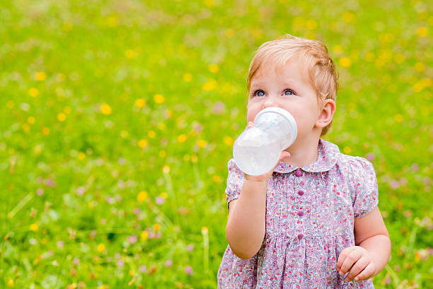 Cute baby drinking water from  bottle outside stock photo