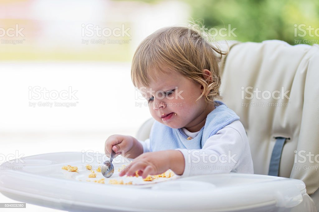 Cute baby eating breakfast in high chair. stock photo