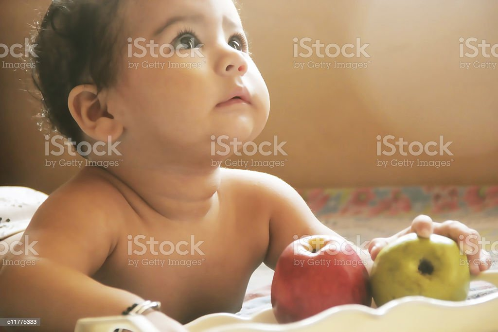 Cute baby eating fruits stock photo