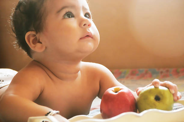 cute baby eating fruits - baby boys stock photos and pictures