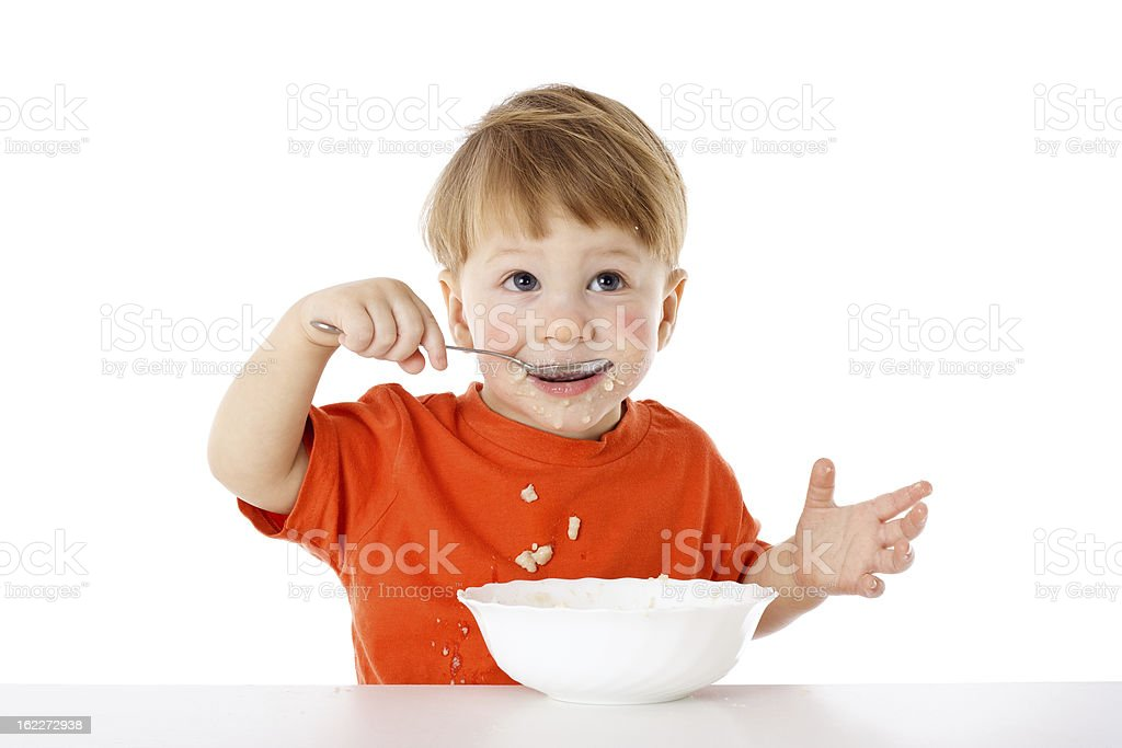 Cute baby eating oatmeal with spoon royalty-free stock photo