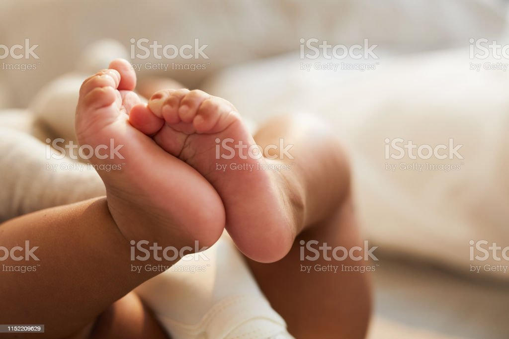 Cute baby feet Close-up of unrecognizable cute baby shaking feet while lying in bed, innocence concept African Ethnicity Stock Photo