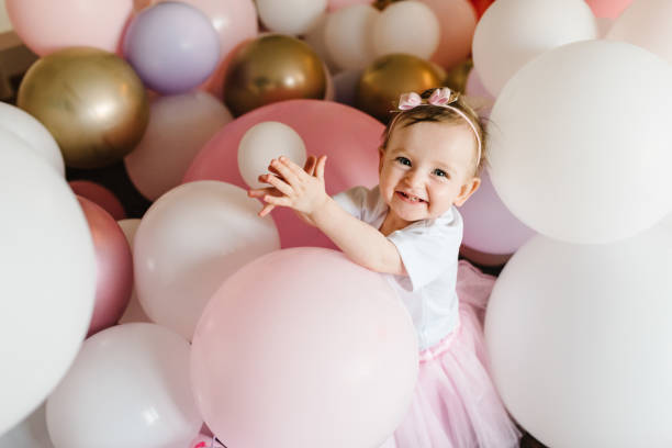 Cute baby girl 1 year play with colorful balloons in the studio. Isolated. Birthday party. Celebration. Happy birthday baby. Play room in home.
