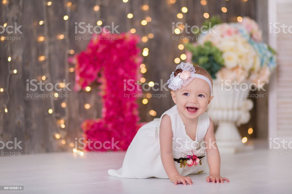 Cute baby girl 1-2 year old sitting on floor with pink balloons in room over white. Isolated. Birthday party. Celebration. Happy birthday baby, Little girl with group ball. Play room. stock photo